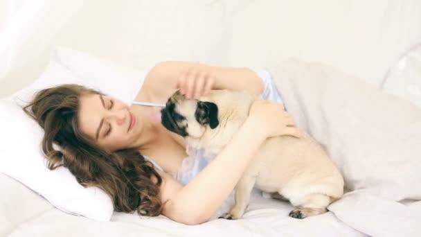 Frau kuschelt mit Mops Hund im Bett. Videomaterial