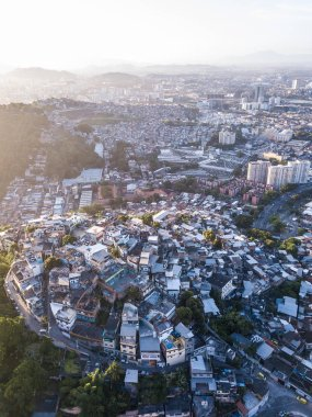 Rio de Janeiro city aerial view. Favelas hills. Sunset backlight. From above. Aerial vertical photo