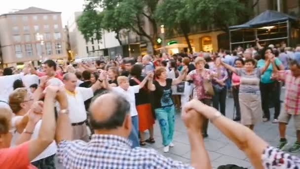 People are dancing on the street in plaza Barcelona Spain. Summer evening. Festivities. Editorial video footage