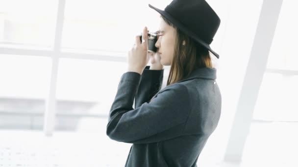 Střelba. Stylová krásná dívka držící vačku v retro stylu. Chyť se toho okamžiku. Video záběry, cestovní bloger