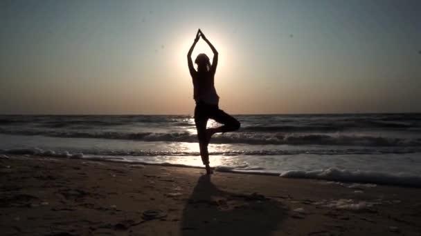 Dívka stojí v józe, naproti slunci při západu slunce, na pláži, na moři
