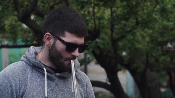 Stílusos, fiatal srác napszemüvegben vízipipát szív egy csőből, füstöt szabadít fel.