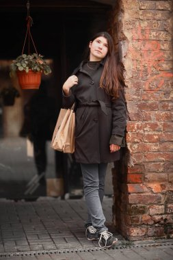 teenager girl with long brown hair street photo with shoping bag on city windowshop background