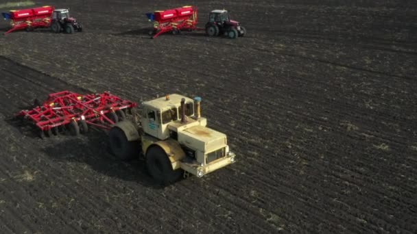 Taken from a drone, red tractors follow each other across the field.