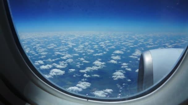 Let letadlem. Křídlo letadla letícího nad mraky se západem slunce. Pohled z okna letadla. Letadlo, letadlo. Cestování letecky.