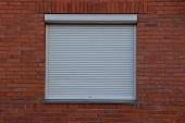A négyzet alakú ablak szürke jalousie tégla falon zárt