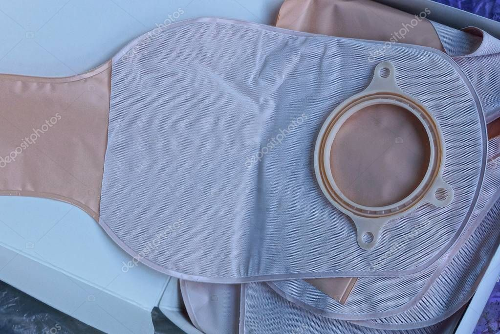 plastic medical colostomy bag lies in a gray paper box