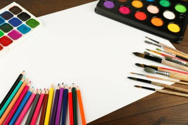 paint brushes, paints and paper are on the table, top view