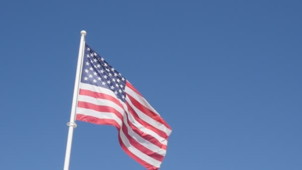 United States of America flag fabric waving on wind against blue sky on background