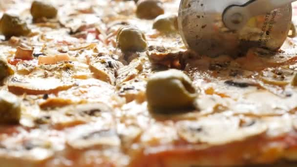 roller-knife cutting Italian warm pizza with cheese and olives , close-up