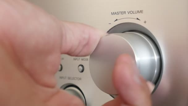 male hand setting master volume level on audio power amplifier, close-up