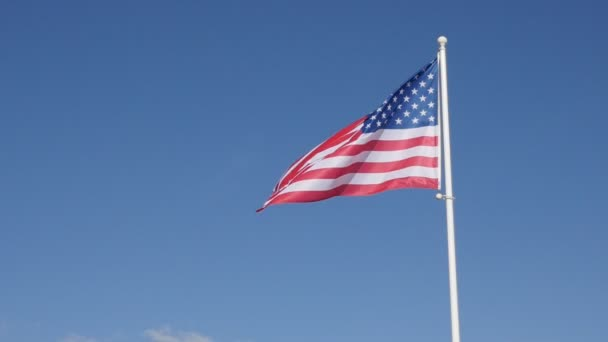 flag of United States of America waving on wind against blue sky on background