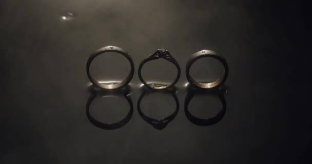 Snubní prsteny a zásnubní prsten ležící na povrchu temné vody zářící světlem zavřete makro. Reflexe