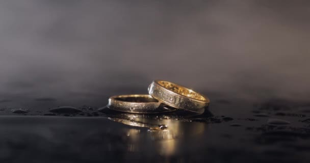 Wedding rings lying on dark water surface shining with light close up macro. Reflection