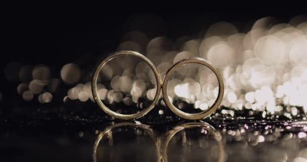 Snubní prsteny na povrchu temné vody zářící světlem zavřete makro. Reflexe