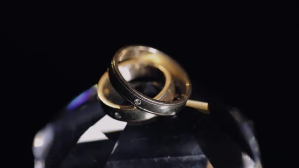 Wedding rings lying on crystal shining with light close up macro. Black background. Slow motion