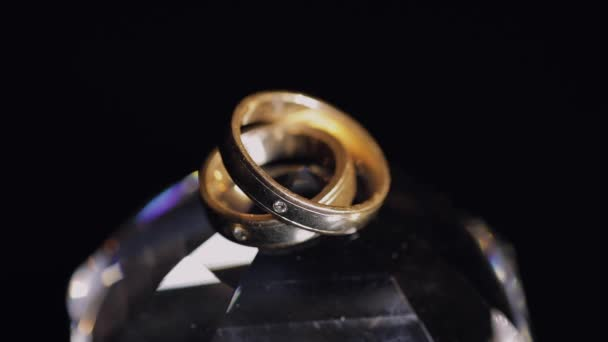 Wedding rings lying on crystal shining with light close up macro. Black background. Slow motion