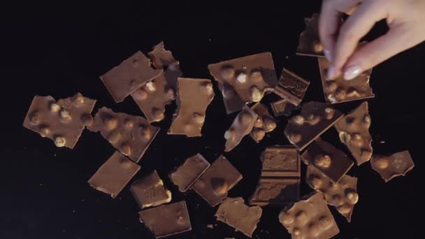 Žena ruku vzít jednu tabulku čokolády z banda kousky čokolády. Zpomalený pohyb