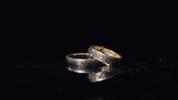 Wedding rings lying on dark surface shining with light close up macro.
