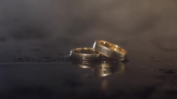 Wedding rings lying on dark surface shining with light close up macro