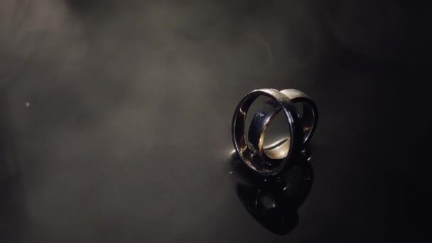 Snubní prsteny na temné vody povrchové zářící světlem. Detailní záběr makro