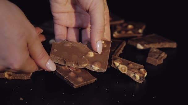 Žena konce černé čokolády s oříšky. Detail. Zpomalený pohyb