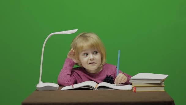 Girl drawing at the table. Education process in classroom. Happy three years old girl. Cute girl smiling. Pretty little child, 3-4 year old blonde girl. Make faces. Green screen video. Chroma Key
