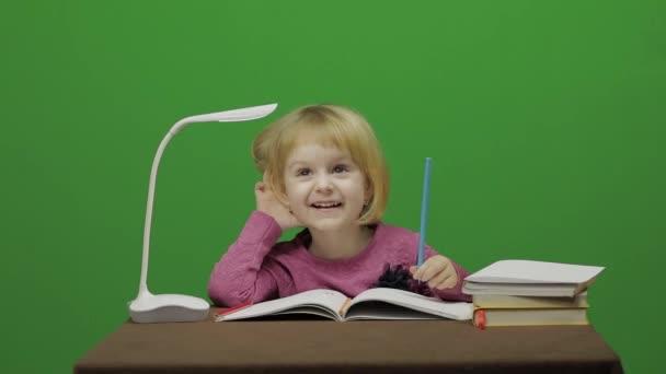 Lány rajz az asztalnál. Oktatási folyamat az osztályteremben. Boldog három éves lány. Aranyos lány mosolyogva. Szép kis gyermek, 3-4 éves szőke lány. Hogy arcok. Zöld képernyős videó. Chroma Key