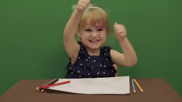Girl at the table.Education. Happy three years old girl. Cute girl smiling. Brown eyes. Pretty little child, 3-4 year old blonde girl. Make faces. Green screen video. Chroma Key