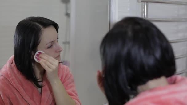 Krásná bruneta žena pomocí vatové tampony. Žena odstranění make-upu