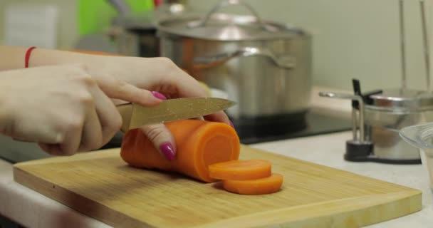 Hausfrau schneidet Möhren in der Küche in Stücke