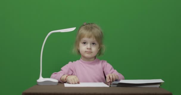 Girl sitting at the table. Education process. Three years old child. Chroma Key