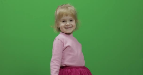 Happy three years old girl. Cute blonde child. Dancing and make faces