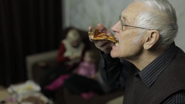 Krásná starší muž v brýlích jí pizzu. Jeho rodina v pozadí