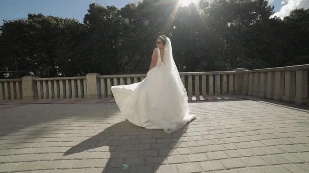 Szép és szép menyasszony esküvői ruha és a fátyol a napsugarak. Lassított mozgás