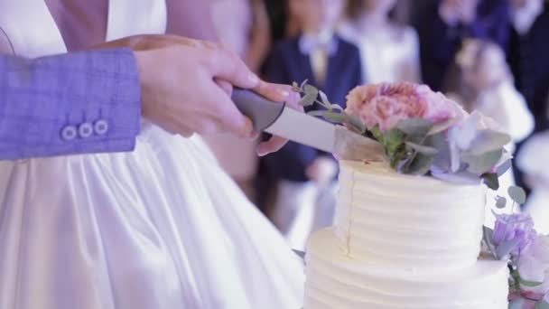 Bride and a groom is cutting their wedding cake. Hands cut of a slice of a cake