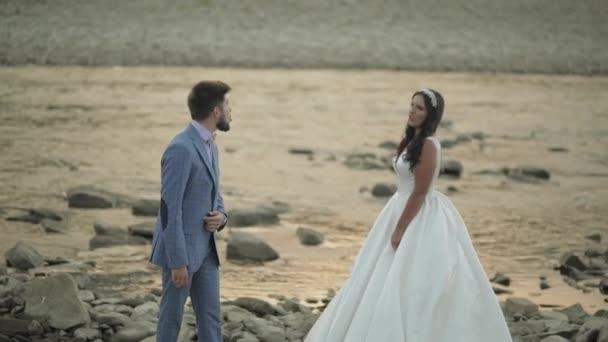 Coppia di sposi in piedi vicino al fiume di montagna. Sposo e sposa fare facce