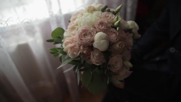 Ženich se svatební kyticí v rukou doma. Bílá košile, Černá kravata, sako