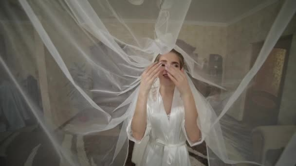 Beautiful and lovely bride in night gown under huge veil. Wedding morning
