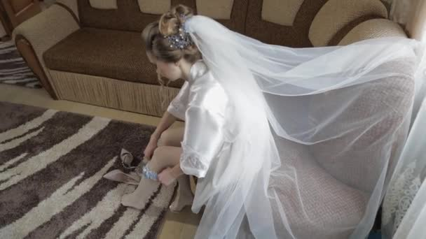 Beautiful and lovely bride in night gown wears wedding garter on her leg