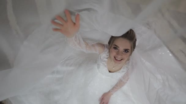 Bride in wedding dress under huge veil. Pretty and well-groomed woman