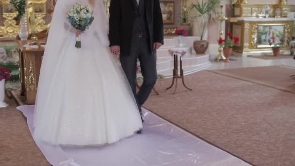 Elegant bride and groom walking together in an old church. Wedding couple
