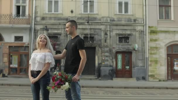 Young and beautiful couple in the center of the street. Slow motion