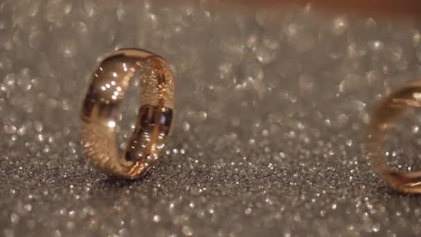 Svatební kruhy na lesklé lesklé ploše. Svítí světlem. Close-up
