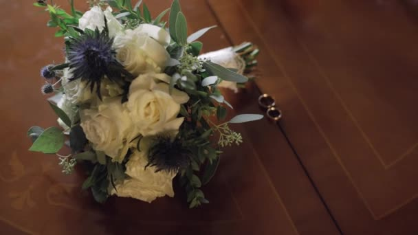 Wedding rings lie near beautiful wedding bouquet on the wooden table