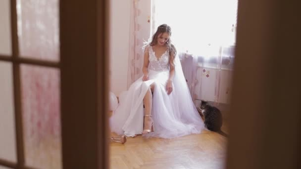 Beautiful and lovely bride in wedding dress sit on a chair and look at her shoes
