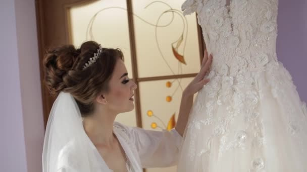 Beautiful and lovely bride in night gown stands near wedding dress. Wedding