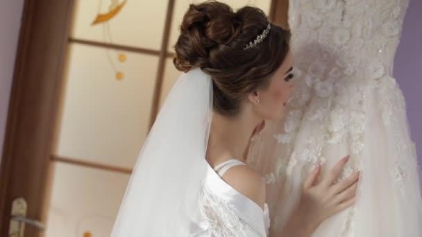 Szép és szép menyasszony éjszakai ruha áll közelében esküvői ruha. Esküvői