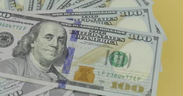 Stovky amerických dolarových účtů se točí. Close-up. Pozadí s dolarovou bankovkami