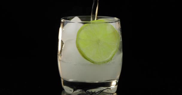 A refreshing drink being poured into a glass with ice, and lime